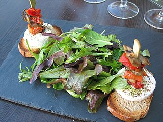 A photo of a mesclun salad and goat cheese on toasts.